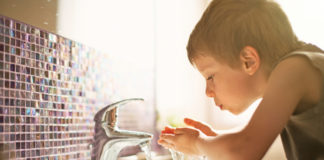 boy drinking from water faucet