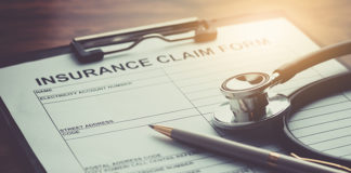 health insurance claim form with stethoscope on wood table selective focus