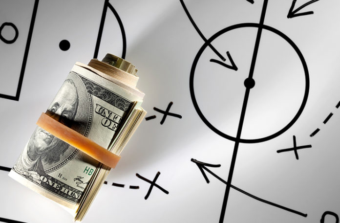 Roll of dollars on a blackboard with strategy planning.