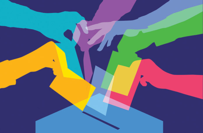 colorful hands putting ballots into a box