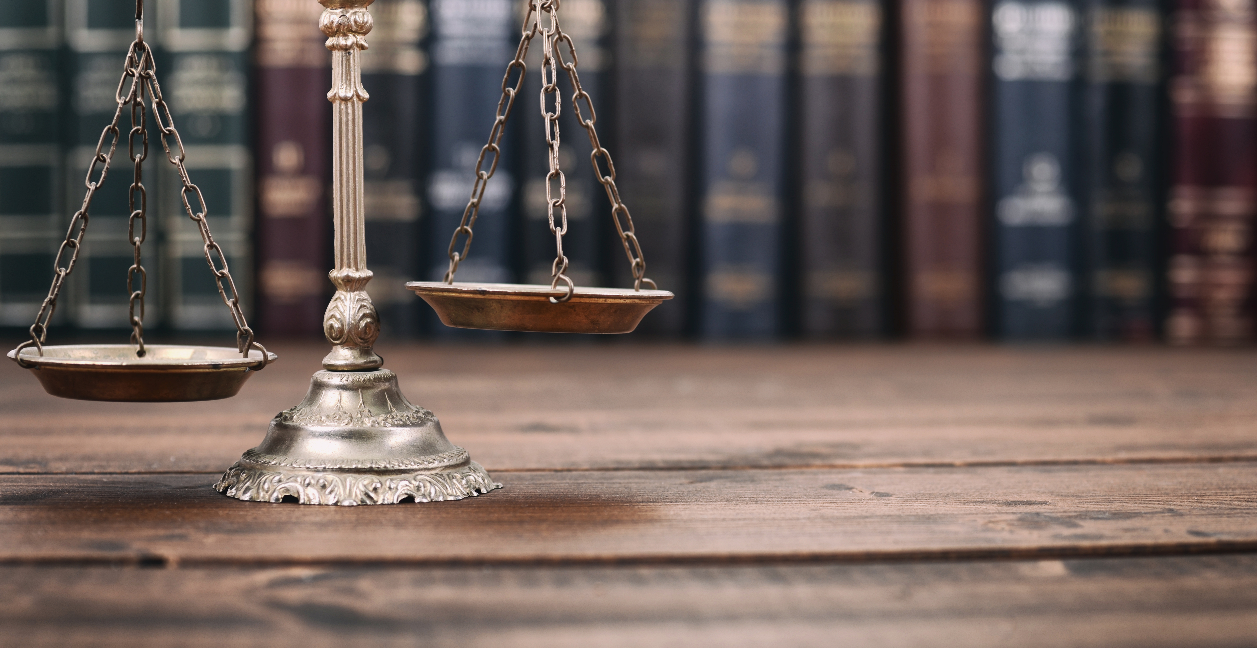 Scales of Justice and Law books on a wooden background