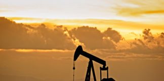 An oil and gas pumpjack silhoutte with dramatic sunset.